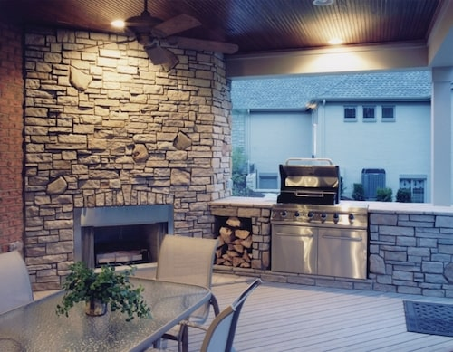 Rear deck with an outdoor kitchen equipped with a built-in grill, a fireplace, and dining table with chairs