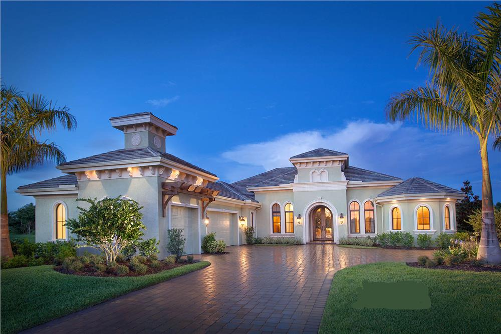 Luxury Mediterranean style L-shape home with stucco siding