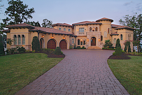 Large Mediterranean style home with 3-car garage that opens onto a front courtyard