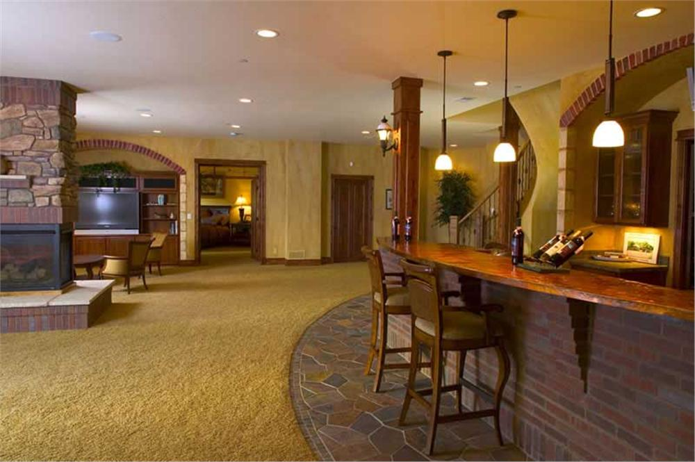 A finished basement with brick finishing a two way fireplace and stone accents.