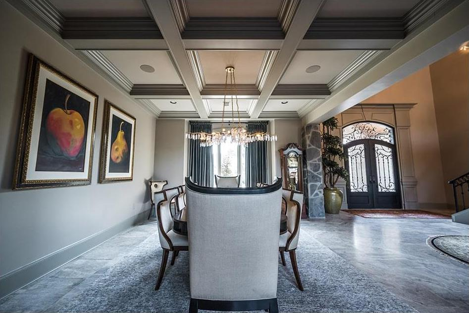 Dark-color woodwork in a coffer ceiling that provides contrast to the white ceiling field
