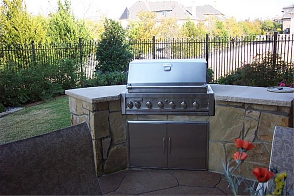Basic outdoor grill built into a backyard patio using stacked stone and countertop
