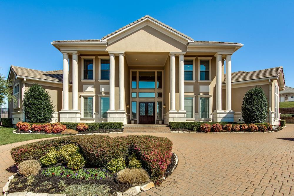 Contemporary Federal style stucco home with doubled front porch columns