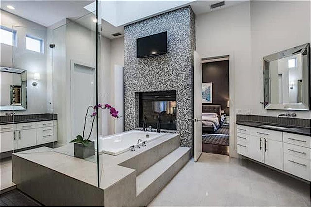 Ceramic-tile-covered accent wall with fireplace and TV