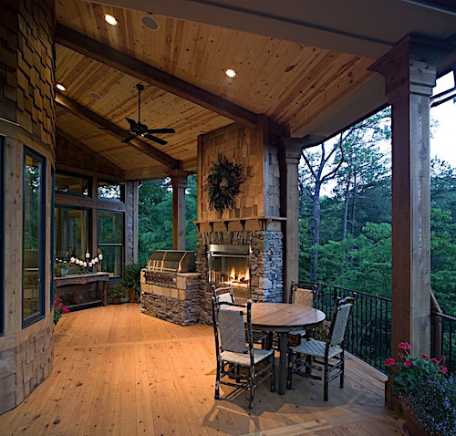 Majestic outdoor fireplace adorning a covered rear porch