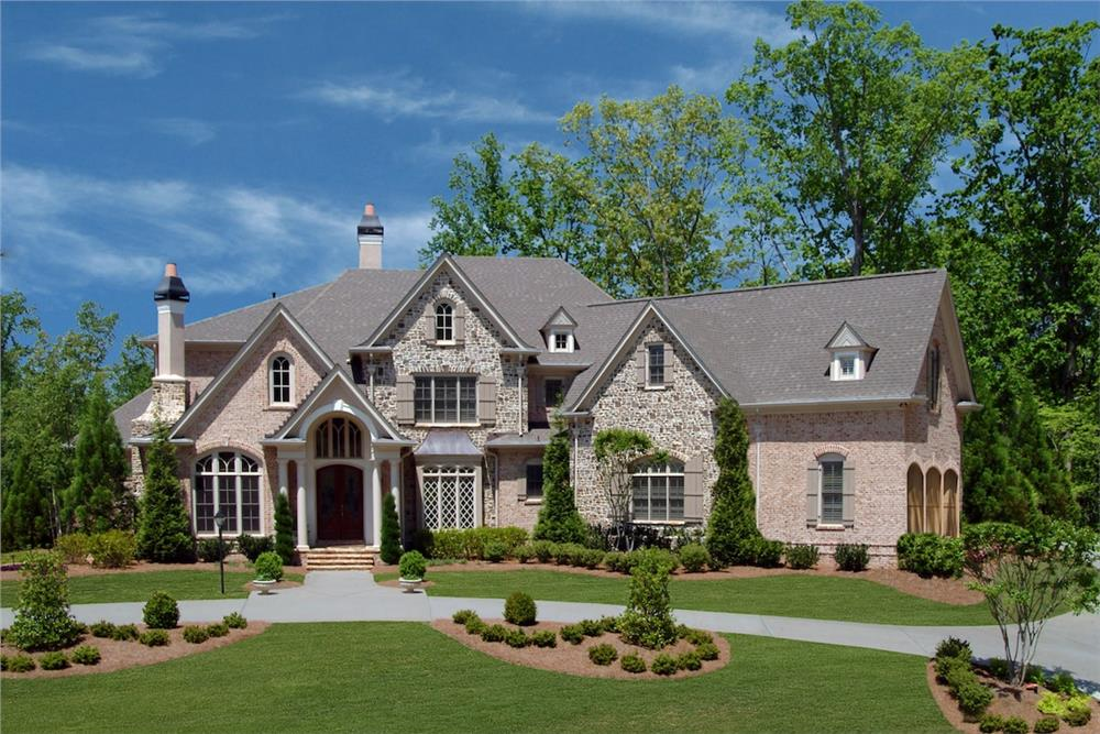 Large Gothic-influenced home with steep rooflines in brick and stone