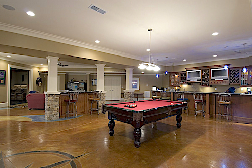 Large recreation area with pool table and bar in luxury rustic home