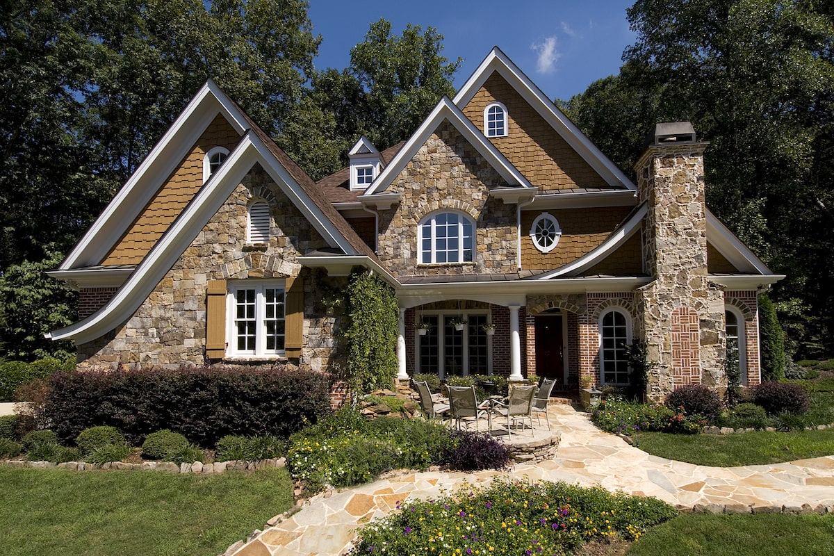 Cottage style home with stone and cedar siding, stone chimney, and steep gables
