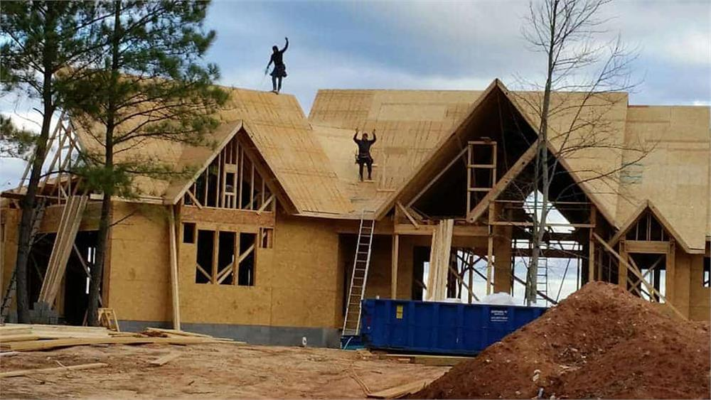 House in process of being sheathed by a carpentry team
