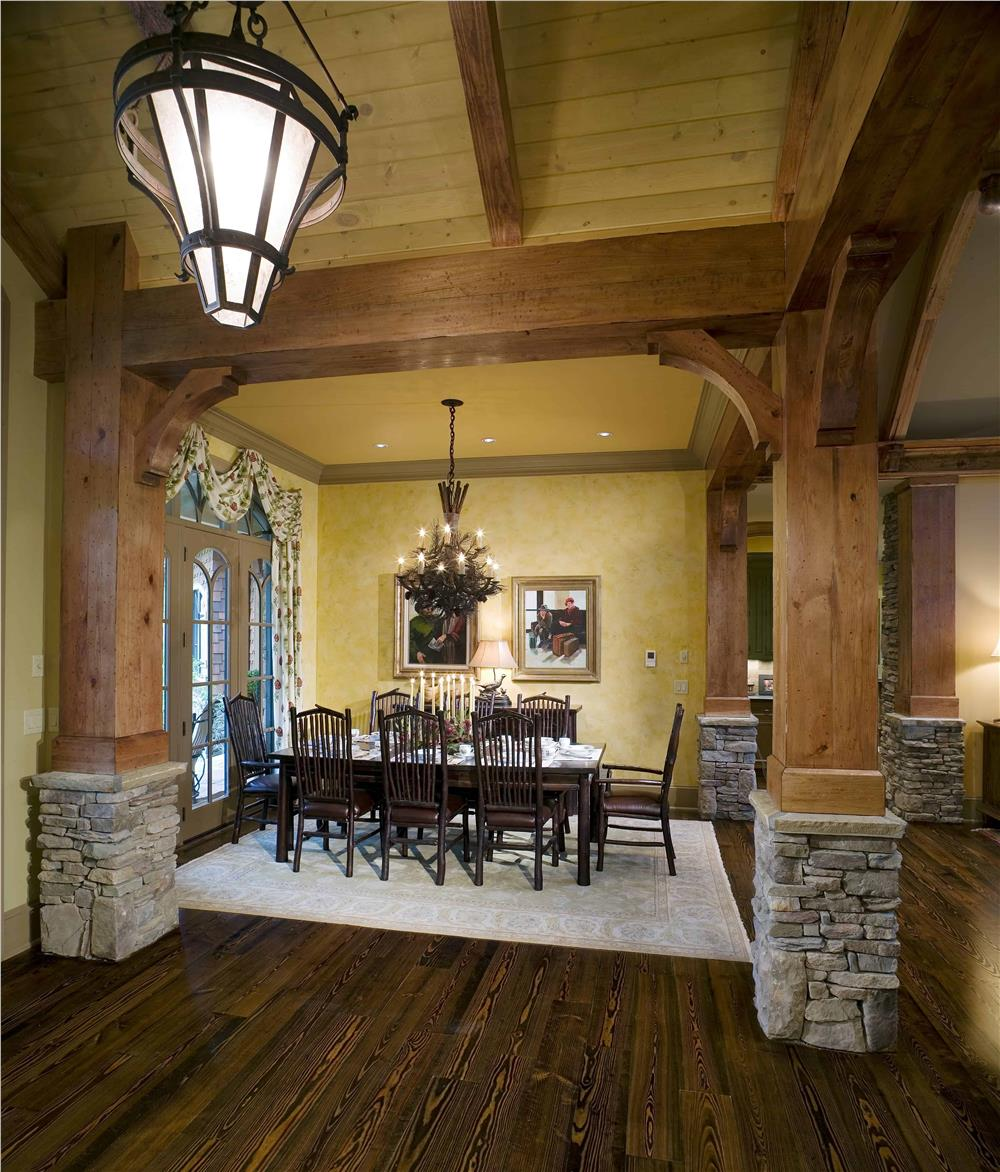 Massive natural wood columns with stone bases enclosing a formal dining space