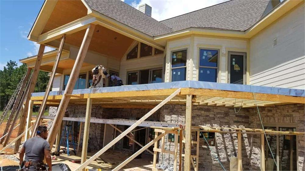 Home under construction being sided with wood siding and stone