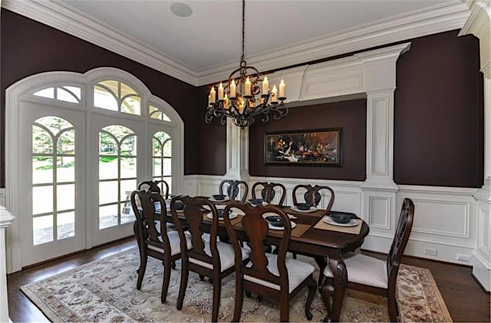 Dark-painted formal dining room with white wainscoting and crown molding