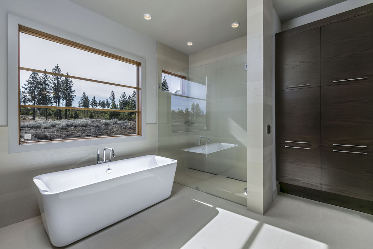 Spare, modern bathroom with standalone tub, nonslip floor surface, and roomy shower