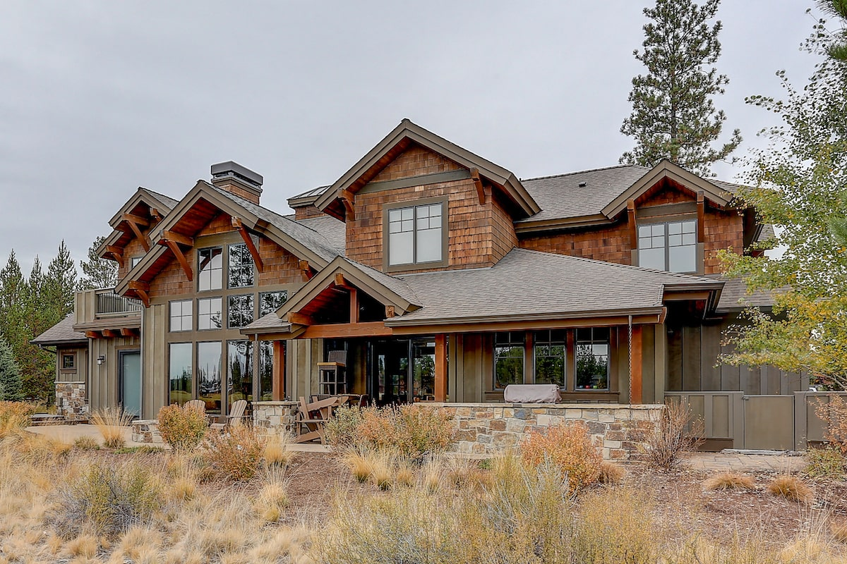 Rear view of rustic home showing stone accent patios and glass expanses