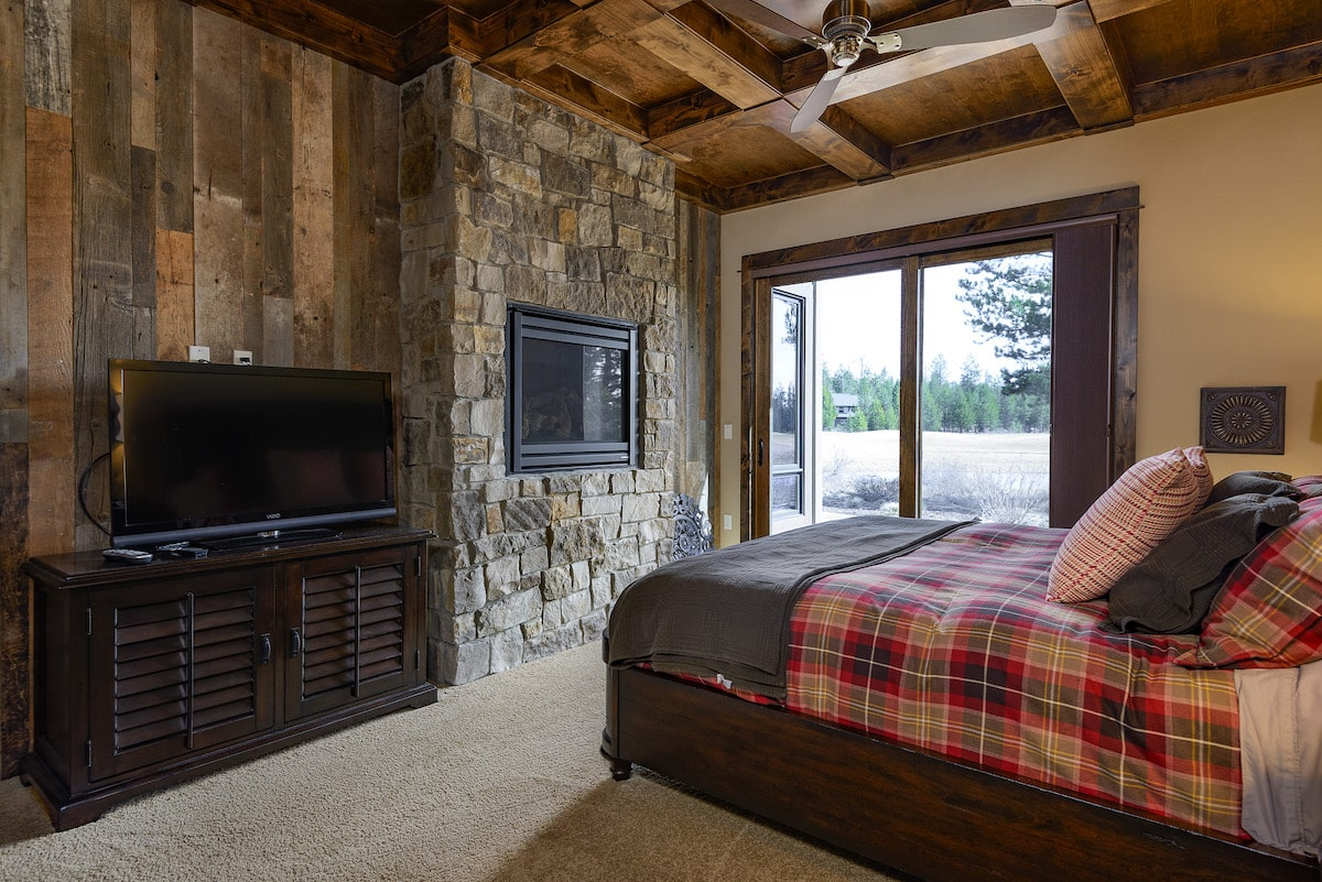 Master bedroom in rustic style home with stone fireplace and wood coffered ceiling