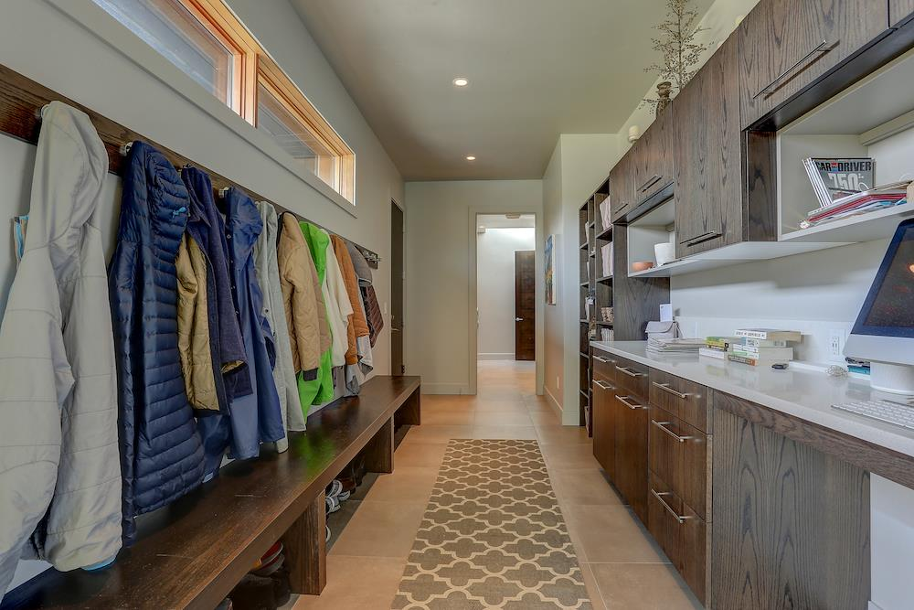 Long mud room with bench, coat hooks, and tech center on the right