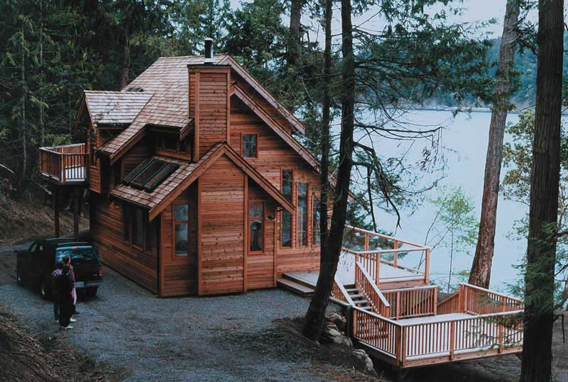 Rustic vacation cabin with natural wood siding looking out on a lake
