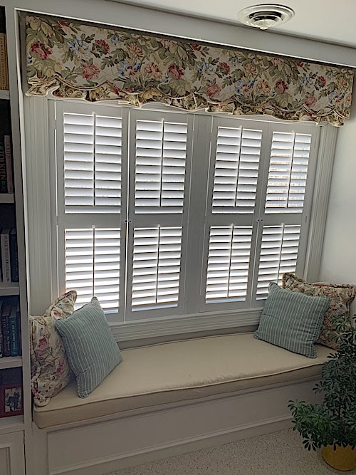 Louvered plantation shutters that control the sunlight at a window seat