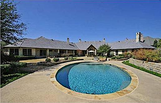 Circular pool in the middle of the backyard of large Ranch style home