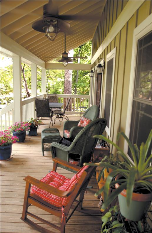 Porch with brightly cushioned rocking chairs.