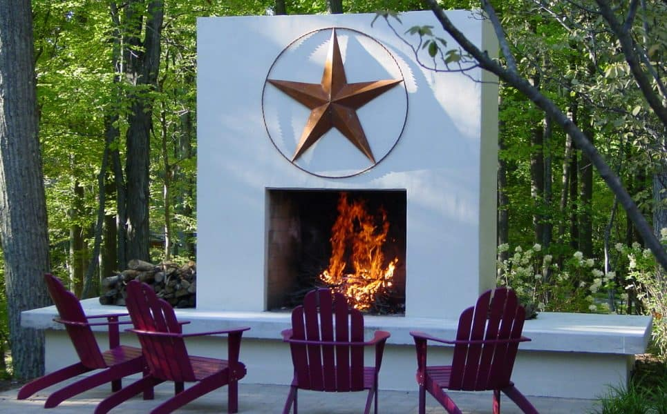 Red Adirondack chairs circled around an outdoor fireplace.