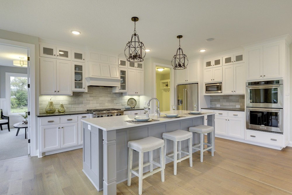 Beautiful white-and-gray L-shape kitchen with glass cabinet doors and stainless-steel appliances