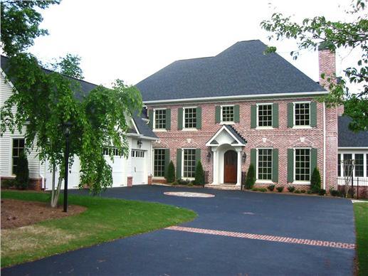 Brick Colonial style home with front portico and attached 3-car garage