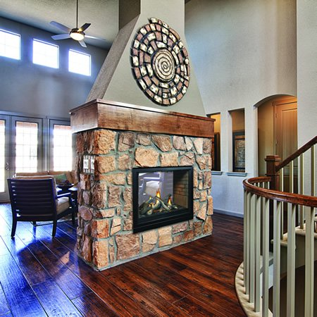 Two-sided fireplace with stone facing
