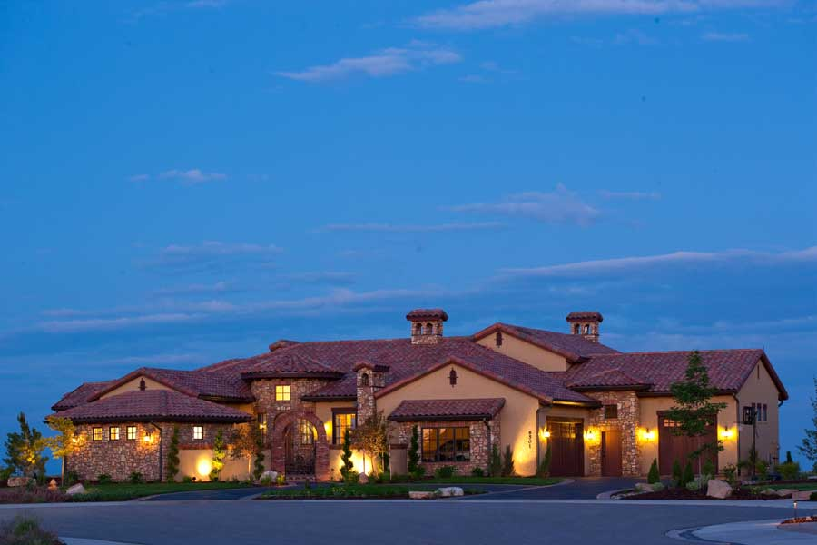 Beautiful Tuscan style home with classic tile roof, beige stucco siding, and stone accents