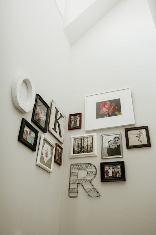 Cluster of art and photos arranged on a corner wall