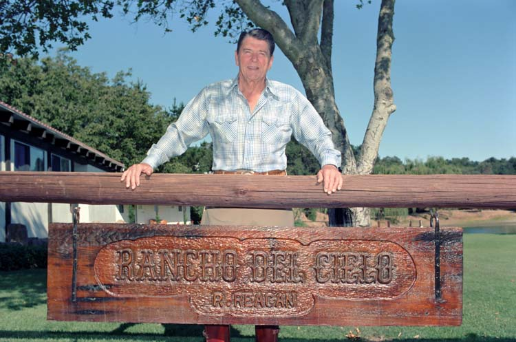 Ronald Reagan behind his Rancho del Cielo sign