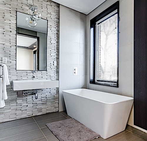 Standalone bathtub with large window and stacked-stone decor