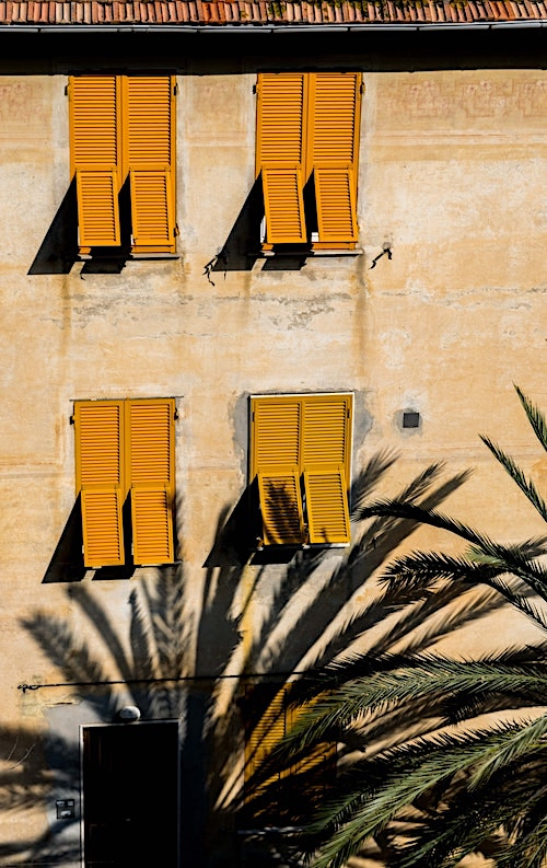 Yellow Bermuda or Bahama shutters on the windows of a tropical home