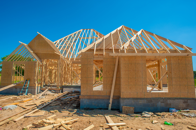 Home under construction with stick-built hip roof