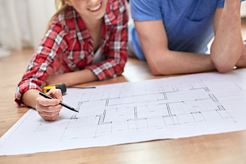 Young couple looking over house blueprints