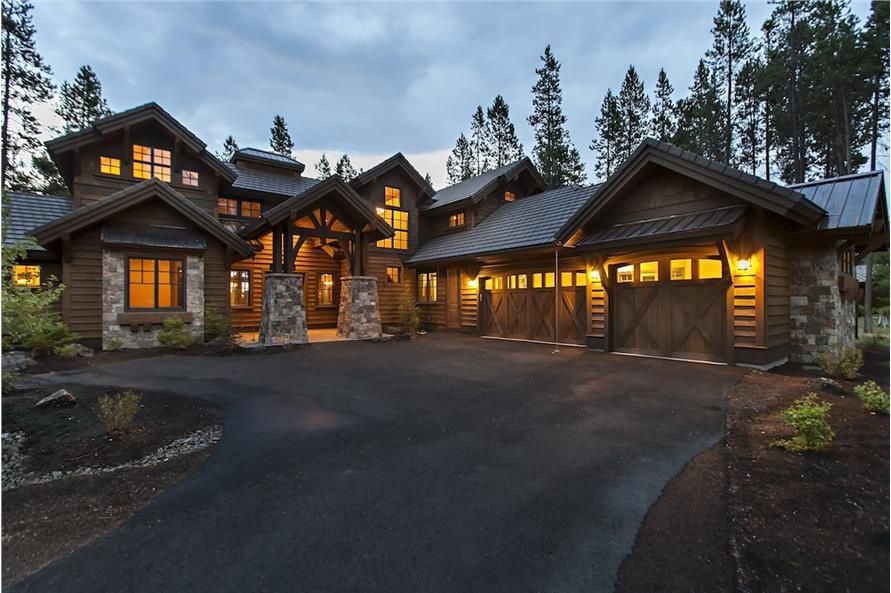 Rustic cabin-style luxury home with stone column bases and timber and metal-roof accents