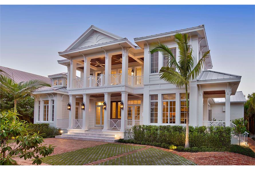 Colonial home with porch columns on both floors, a gable roof, and large multi-pane windows