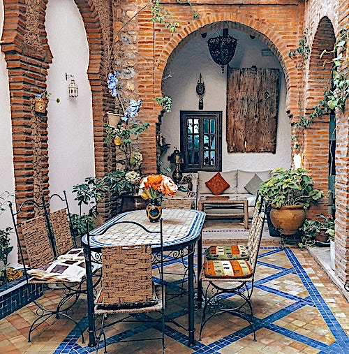 Patio with table and chairs that have colorful seat cushions
