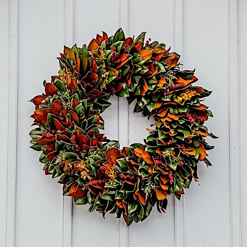 Late-summer wreath of leaves, berries, cuttings on a white door