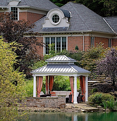 Backyard gazebo by the water adorned with colorful drapes