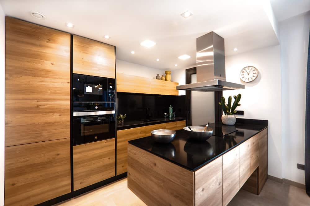 bold single wall kitchen by using wood and black appliances plus black granite counters