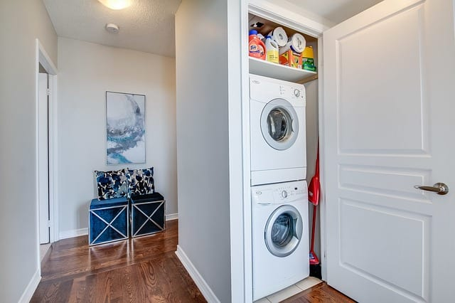 stacked washer and dryer in small hallway closet with storage on top